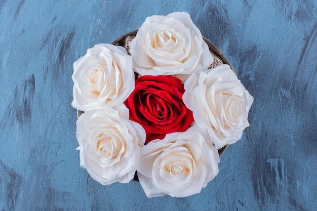 Un bol ancien avec de belles roses fraîches blanches et rouges
