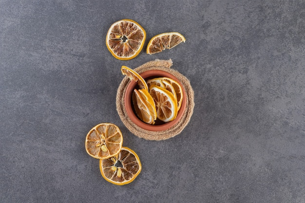 Bol en argile de citrons tranchés séchés sur fond de pierre.