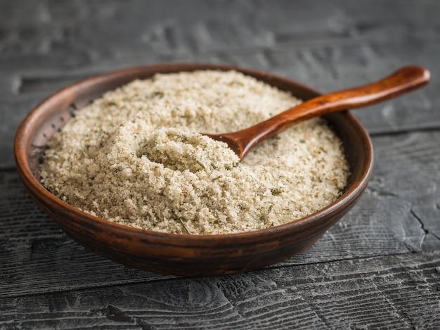 Bol en argile avec une cuillère remplie de sel aux herbes sur la table en bois rustique sombre