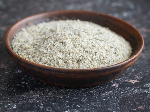 Bol en argile avec une cuillère remplie de sel aux herbes sur la table en pierre sombre