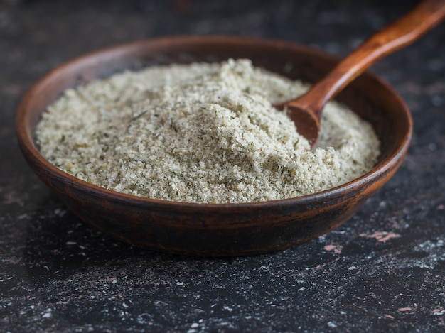 Bol en argile avec une cuillère remplie de sel aux herbes sur la table en pierre.