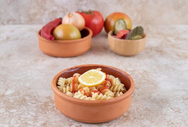 Un bol d'argile de délicieuses pâtes avec divers légumes