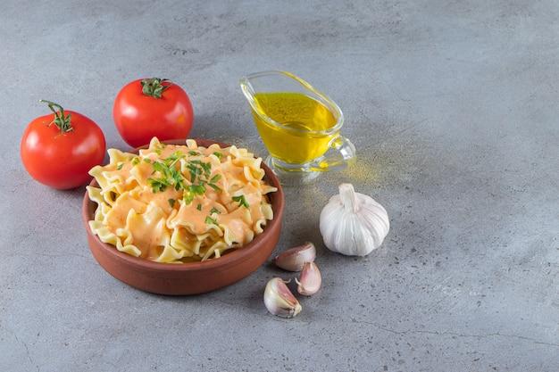 Bol d'argile de délicieux macaronis crémeux avec de l'huile et des légumes sur fond de pierre.