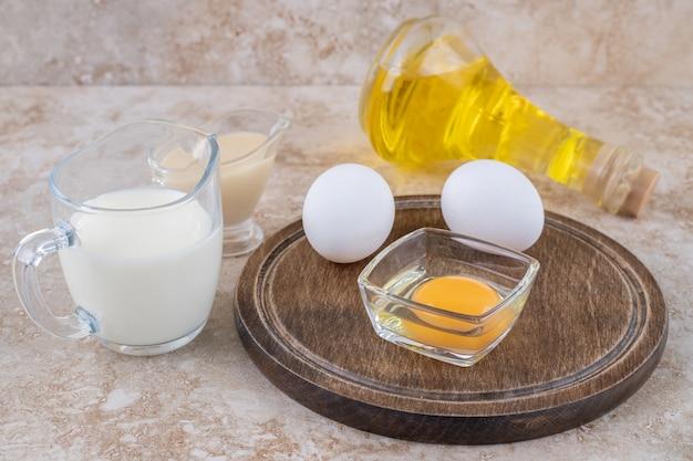 Un bol en argile de fromage cottage avec du lait et une bouteille en verre d'huile