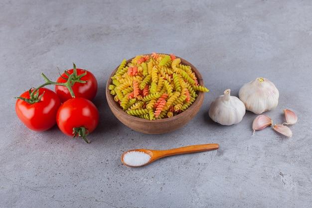 Un bol d'argile de pâtes spirales crues multicolores avec de l'ail et des tomates rouges fraîches.