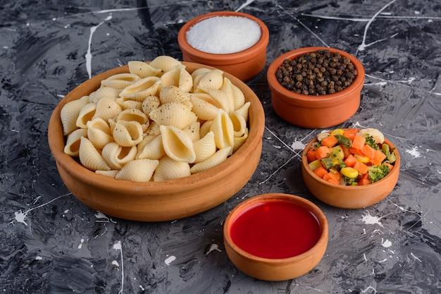 Un bol d'argile plein de pâtes aux coquillages avec sauce tomate sur une surface en marbre