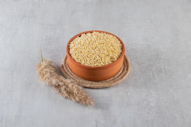 Bol en argile plein de riz cru placé sur fond de pierre.