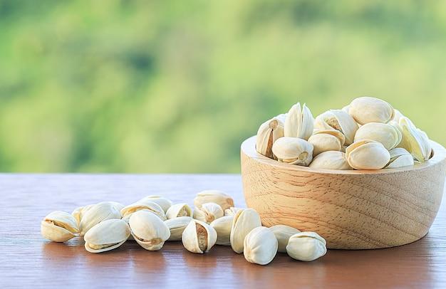 Bol aux pistaches dans une table en bois sur fond de nature floue, copiez l'espace.