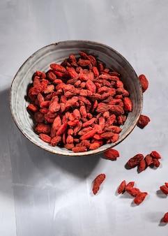 Bol de baies de goji séchées rouges sur fond gris clair avec espace de copie.