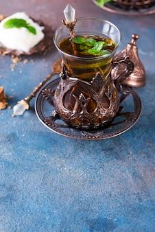 Bol avec barbe à papa turque pismaniye et thé noir à la menthe sur fond sombre,