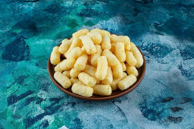 Un bol de bâtonnets de maïs sucré sur bleu.