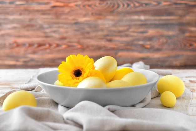 Bol avec de beaux oeufs de pâques sur table
