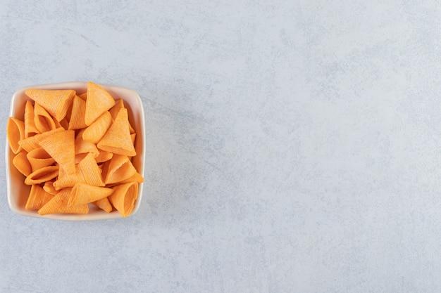 Bol beige de chips croustillantes en forme de triangle sur fond de pierre.