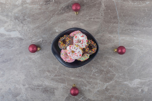 Bol de beignets et boules de noël sur une surface en marbre