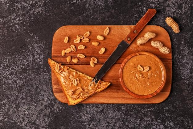 Bol de beurre d'arachide sur planche de bois