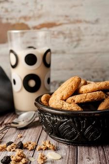 Bol avec des biscuits à l'avoine faits maison et un verre de lait derrière