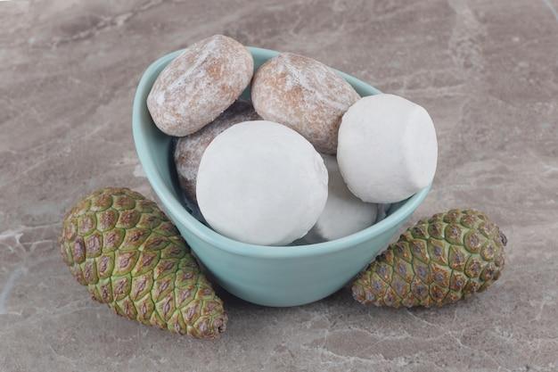 Un bol de biscuits à côté de pommes de pin sur marbre