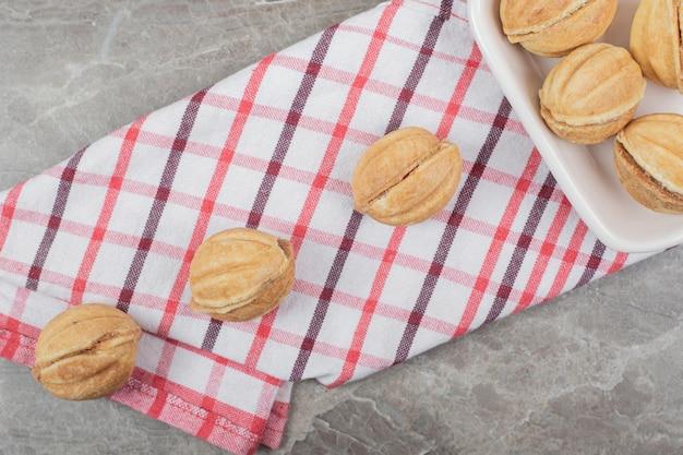 Bol de biscuits en forme de noix sur nappe.