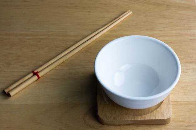 Bol blanc en céramique vide isolé sur le sol en bois.
