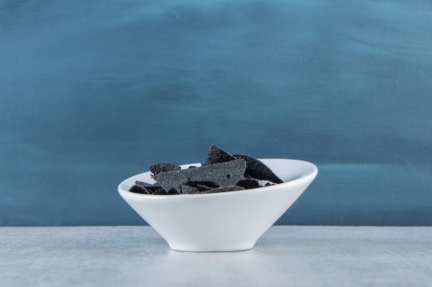 Bol blanc de chips noires croustillantes salées sur pierre.