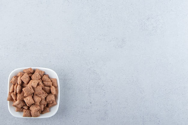 Bol blanc de cornflakes au chocolat sur la surface de la pierre