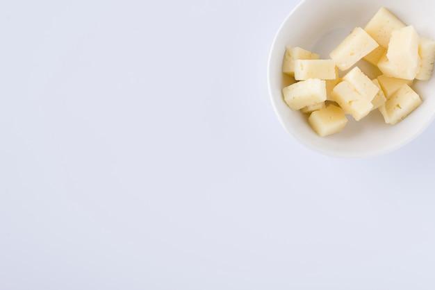 Bol blanc dans un squere avec des morceaux de délicieux fromage pecorino sur fond blanc