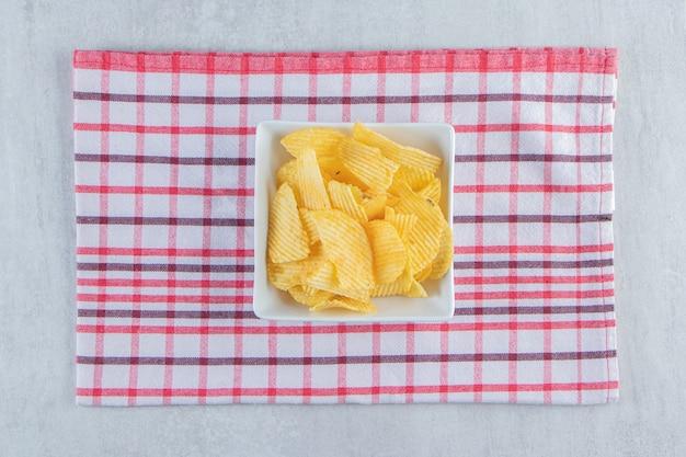 Bol blanc de délicieuses chips d'ondulation sur pierre.