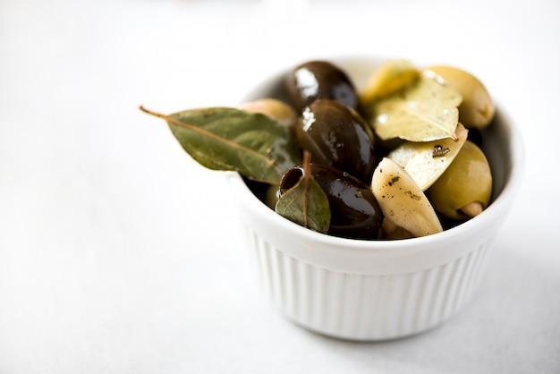 Bol blanc avec olives fraîches noires et vertes, ail, feuilles de laurier sur fond gris.