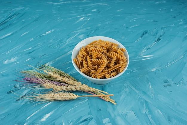 Bol blanc de pâtes fusilli sèches avec des épis de blé sur fond bleu.