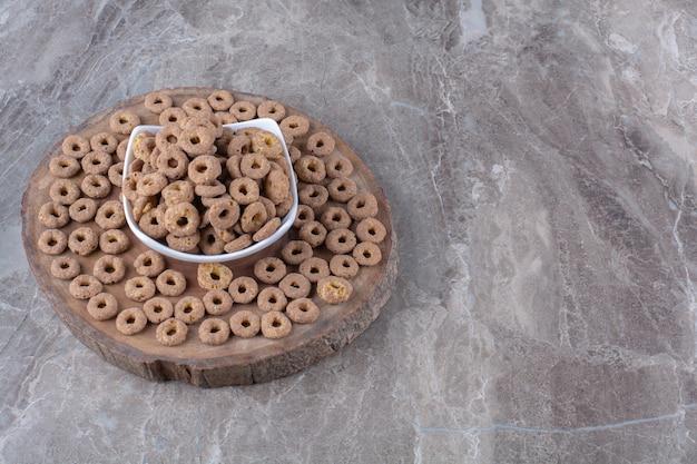 Un bol blanc plein d'anneaux de céréales au chocolat sain sur une pièce en bois.