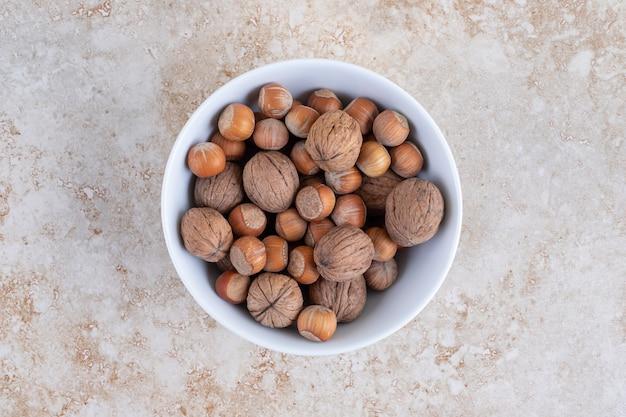 Un bol blanc plein de noix de macadamia saines et de noix placées sur une surface en pierre.