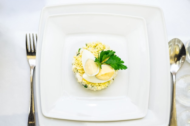 Bol blanc de salade aux œufs farcis sur table