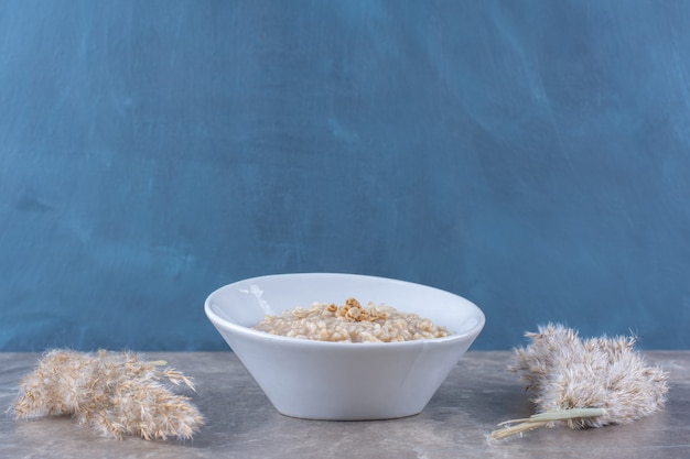 Un bol blanc avec une savoureuse bouillie d'avoine saine pour le petit-déjeuner.
