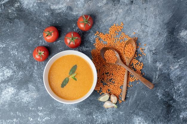 Un bol blanc de soupe aux lentilles avec des tomates et des cuillères en bois.