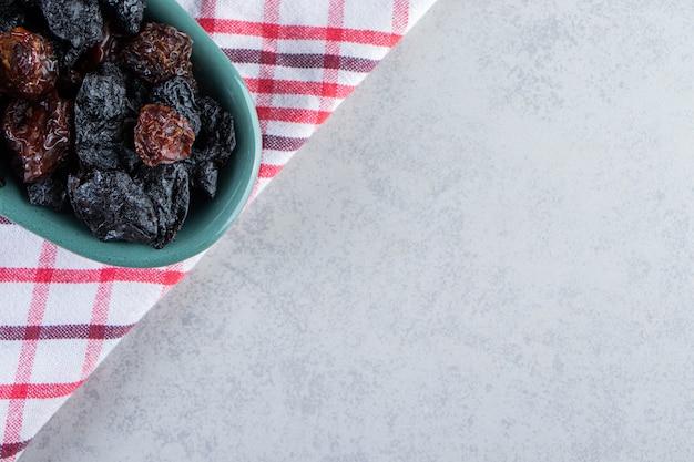 Bol bleu de délicieuses dattes séchées sur pierre.