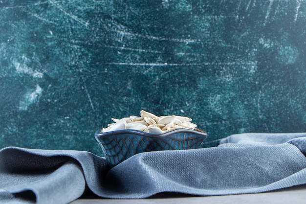 Bol bleu de graines de citrouille avec tissu bleu sur fond de pierre.