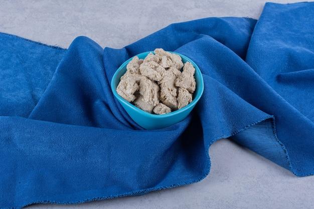 Bol bleu de halva de tournesol savoureux sur table en pierre.