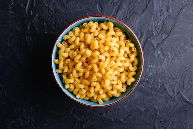 Bol bleu avec des pâtes frisées de blé doré non cuit cavatappi sur table noir foncé texturé, vue de dessus