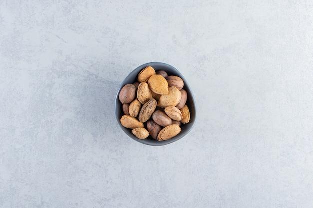 Bol bleu plein d'amandes et de noix décortiquées sur fond de pierre.