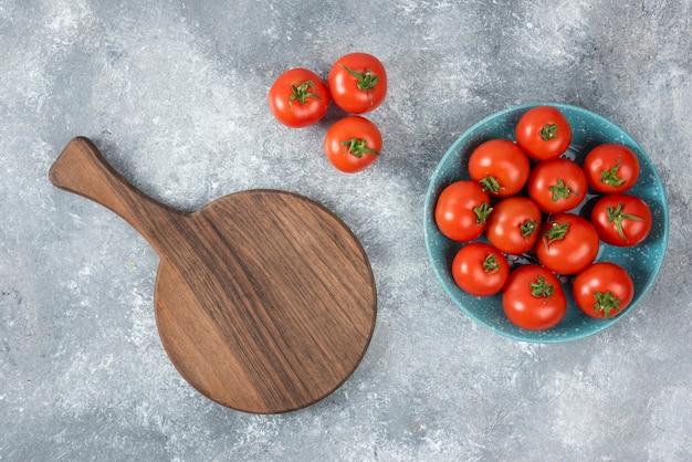 Bol bleu plein de tomates fraîches rouges sur marbre.