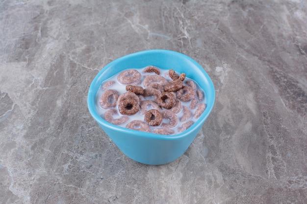Un bol bleu profond avec des céréales saines et du lait sur fond gris.