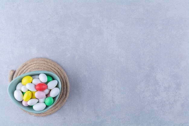 Un bol bleu profond rempli de bonbons aux haricots colorés sur une surface grise
