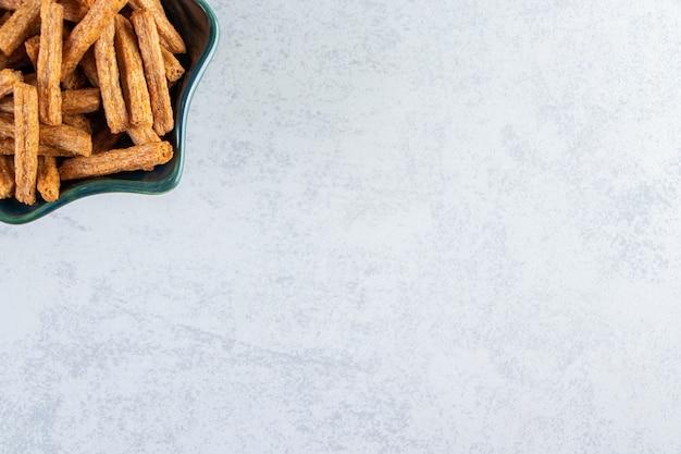 Bol bleu de savoureux crackers bâton sur fond de pierre.