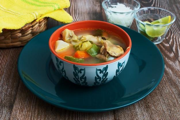 Bol bleu avec soupe au poulet sur bois