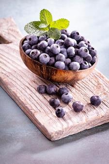 Bol de bleuets frais sur planche de bois rustique. myrtilles d'aliments biologiques et feuille de menthe pour un mode de vie sain.