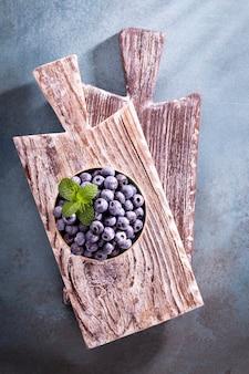 Bol de bleuets frais sur planche de bois rustique