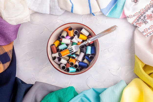 Bol avec bobines de fil et fourche dans un cadre en tissu multicolore
