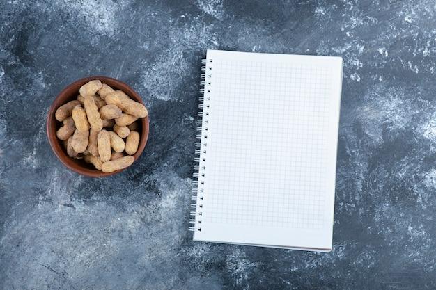 Bol en bois d'arachides décortiquées bio avec cahier vide.