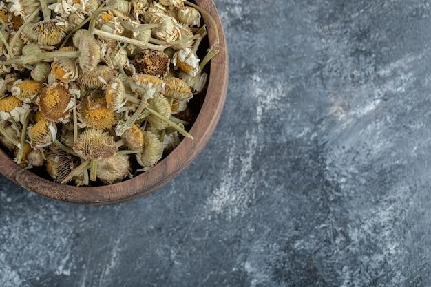 Bol en bois de camomille séchée sur table en marbre.