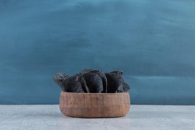 Bol en bois de chips noires croustillantes sur pierre.